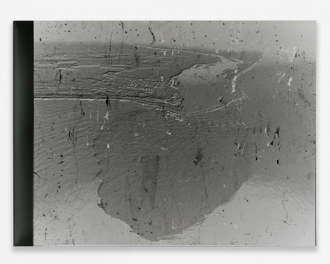 A grey photograph of an aerial view of the BP Oil Spill in the ocean, with small flecks upon the surface. The photograph is mounted on black plexiglass.