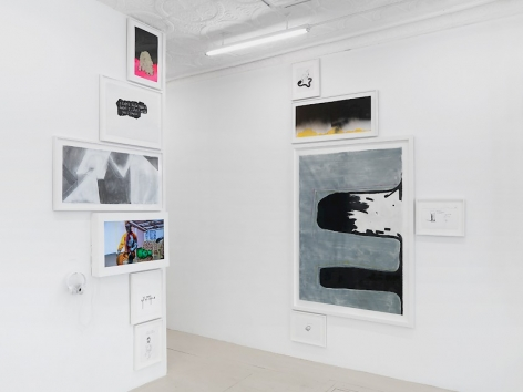 An installation image of the entryway into the gallery office, which hosts 2 columns of drawings and paintings: one on the edge of a wall, and the other directly opposite it (90-degrees). The entryway is the central line of this arrangement.
