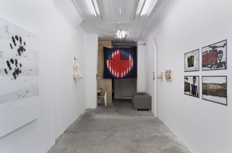 A photograph of the entire gallery: paw paintings on the left, an American flag artwork, and 4 collage photographic works on the right wall.