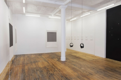 A view of the gallery where the photograph is taken from the front of the room. The 2 headphones are hanging in the center of the room. At left are 2 screenprints stretched at each corner and off the wall. There is another work on the back wall of the gallery. Along the right wall leading to the office are small works installed on the wall, framed in white.