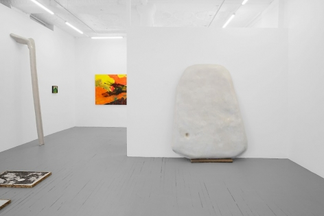 A photograph of the gallery where we see the temporary wall with a large white sculpture upon it. There is a partial view of a colorful painting on the back wall and a smaller painting at left of that. There is a large sculpture leaning against the wall at left, and a print installed on the ground near the left-corner of the photograph.