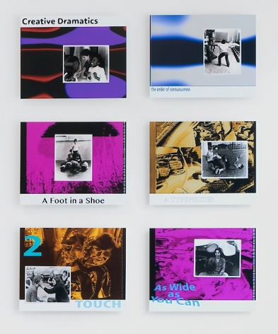 An installation of 6 rectangular lobby card artworks hung on the wall in 2 columns of 3. Colors are mostly purple, yellow, orange, blue, with black and white photographs.
