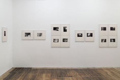 A photograph of the back wall of the gallery, which illustrates 13 images in cream mattes with silver frames.