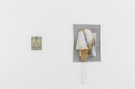 A photograph of two artworks on a single wall: at left is a small print with details illegible and at right is a work with fabric collaged over a window screen that is framed.