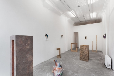 A photograph from the front of the gallery with 6 sculptures on the ground and 4 photo works on the 3 walls