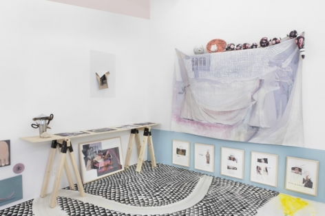 A photograph of the gallery's site-specific installation. At right is a work on fabric with small sculptures above it. At left is a table made of plywood and 2 sawhorses that hold more flat works. There are also works beneath the table at left and right, framed in natural wood. Contents are illegible.