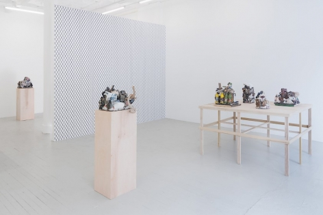 A photograph of the main area of the gallery: at right is a square raw platform with 4 ceramic sculptures upon it. On the temporary gallery wall is a wallpaper visualizing a chainlink pattern in black and white. There are also 2 raw wood pedestals with one sculpture on them, respectively.