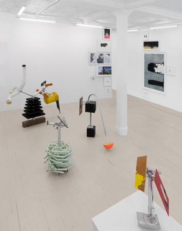 An installation view showing a cluster of 4 sculptures and two walls with drawings hung in a column