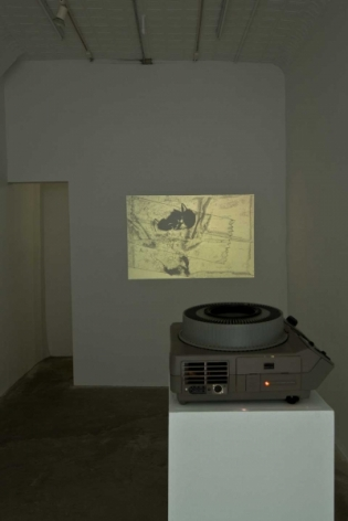 A photograph of the projector throwing an image onto the back wall. The projector is on a white pedestal