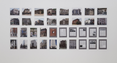 A group 36 photographs of exteriors of banks, hung on the wall in 4 rows