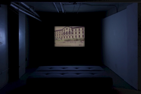 A photograph of a dark room with a video on the far wall. There is a cushioned bench in the middle of the room. The film is frozen on a still of the Ohio State Penitentary.