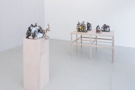 A photograph of a single raw wood pedestal with a ceramic sculpture upon it. In the background we see a raw wood platform with 4 ceramic sculptures upon it. At left, we see the chainlink fence wallpaper on the gallery's temporary wall.