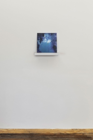 A photograph of Tom Martin's work on aluminum, installed on a white shelf.