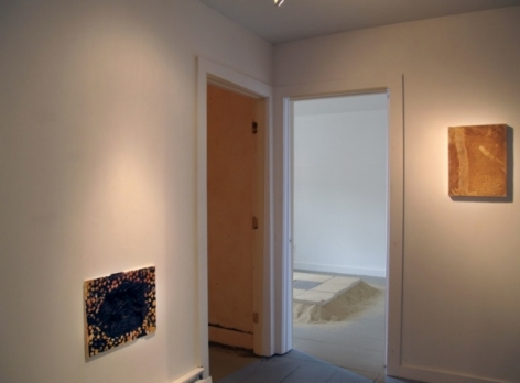 A photograph of 2 flat works on 2 walls. The doorway shows the site-specific tile work in the background