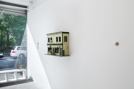A photograph of the gallery interior with the window at left. On the white wall, starting at the window: a small traffic sign; a 3D sculpture of a yellow building facade, a small brown bag. In front of the window is a white bench with 3 small paper trees at right on the bench.