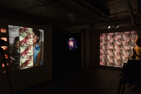A photograph of the gallery's basement, which hosts 3 videos on 2 walls facing one another. They are tessellated images that include varied medical images and portraiture