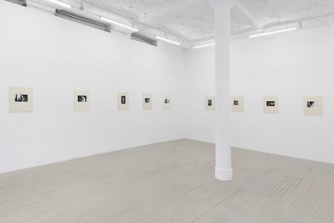 Installation image of 9 black and white Hervé Guibert photographs, placed in cream-colored frames made from watercolor paper, hung on the wall