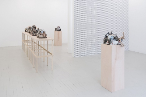 A photograph of the long raw wood platform holding 5 ceramic sculptures, and 2 sculptures on raw wood pedestals (1 each respectively), one in the foreground, one in the background. The chainlink fence wallpaper is visible in the middle ground.
