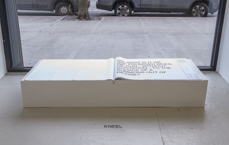 A book, black text on white pages, installed on a custom white pedestal in front of a window, with instructions on the floor to KNEEL