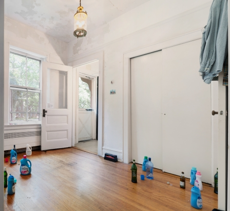 A photograph of the room with detergent bottles and liquor on the ground, open, and a shirt on the door at right