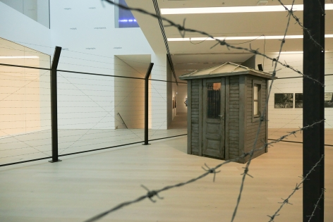 Hale Tenger, We didn't go outside; We were always on the outside/ We didn't go inside; We were always on the inside, 1995, Guard house found on site, barbed wire, pocket radio,, tea cup, fat, etc. and audio, 1400 x 600 x 240 cm
