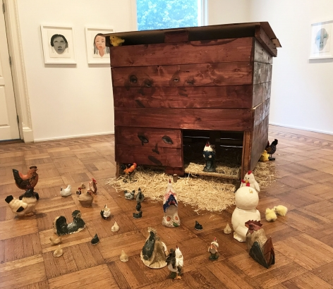 Installation work by February James consisting of a wooden chicken coop with faces painted on each side and tens of found ceramic chickens on the floor.