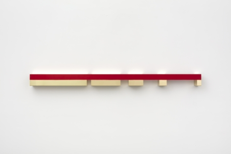 Donald Judd's untitled polished brass and red anodized aluminum sculpture, created 1974-75, installed on wall, measuring 5 x 75 x 5 in. (12.7 x 190.5 x 12.7 cm)