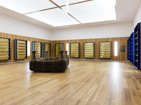 Mucha sculpture installation, wood paneled room