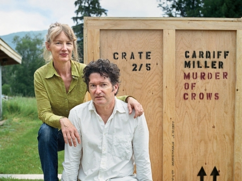 a man and a woman in front of a wooden crate