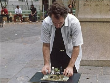 man looking at chessboard on table