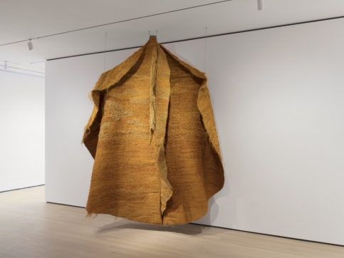 Installation view of orange hanging textile piece by Magdalena Abakanowicz