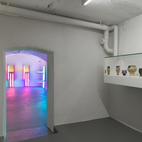Installation view of fluorescent light sculptures by Dan Flavin and pottery by Lucie Rie and Hans Coper