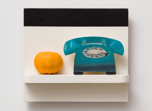 a phone and an orange on a painted white and black shelf