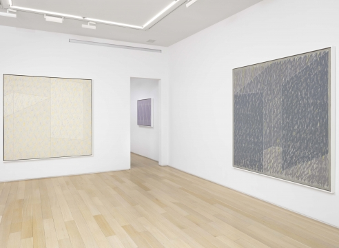 two abstract paintings in a white room