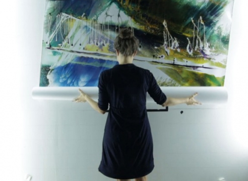 image of a woman holding a large scroll photograph on the wall