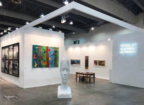 Art fair booth featuring sculpture and paintings