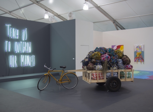 Art fair booth featuring neon text, bicycle sculpture, and paintings