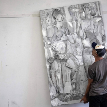 image of a man moving a large silver painting