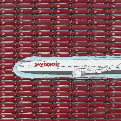 A Swissair airplane painted over a group of red Swiss Army knives on plywood by Tom Sachs