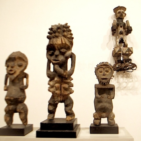 Four wood sculptures of humanoid, geometric shapes face us directly. Three of them are standing on a white block mount, and another is mounted on the white wall to the left.