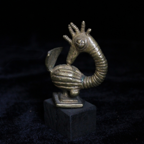 Small gold sculpture of a cartoonish bird with prominent carved stripes. Its eye resembles a button and it has a crown of feathers on the top of head which are small and cylindrical.