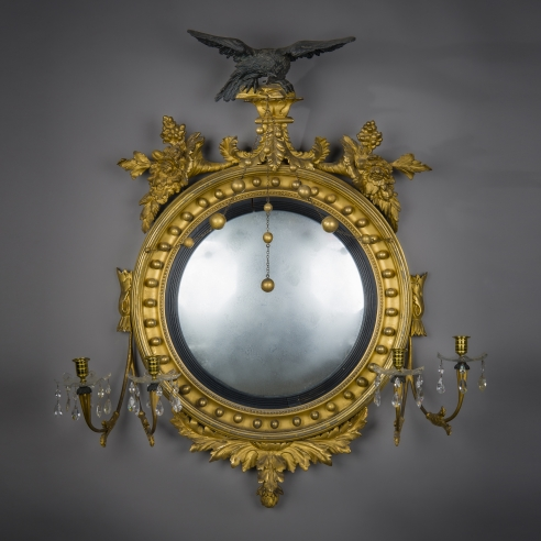 Neo-Classical Convex Girandole Mirror with Candle Arms, about 1810. American, probably Salem, Massachusetts. Eastern White Pine, gessoed and gilded, and partially ebonized, with convex mirror plate, glass drip pans, blown and cut, glass prisms, gilt-brass candle cups and bobeches, and brass chain 43 in. high, 38 in. wide, 10 5/8 in. deep.
