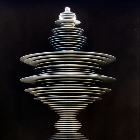 a sculpture by Elizabeth Turk of aluminum discs stacked and arranged to simultaneously resemble a Modernist abstraction and a sound wave