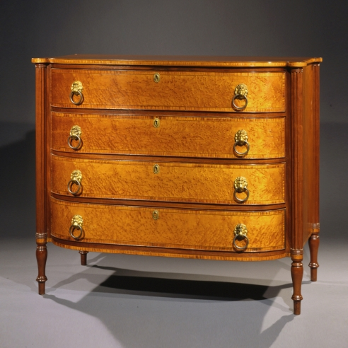 Bowfront Chest of Drawers in the Sheraton Taste, about 1815 Eastern Massachusetts, probably Boston, possibly Thomas Seymour. Cherry, mahogany, bird's eye maple, striped maple, and ebony, with original gilt-brass lion-head pulls. 37 5/16 in. high, 43 5/8 in. wide, 23 7/16 in. deep