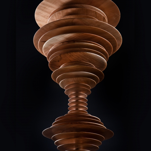 close-up view of a totemic wood sculpture by Elizabeth Turk featuring thin discs layered on each other to resemble a sound wave