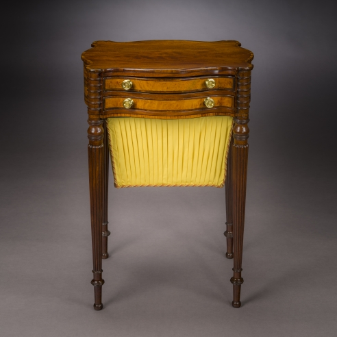 Work Table in the Sheraton Taste, about 1810. Attributed to Thomas Seymour, Boston. Mahogany, striped and bird's eye maple, and ebony, with gilt-brass drawer knobs, and fabric work bag, 27 3/4 in. high, 19 1/4 in. wide, 15 3/4 in. deep