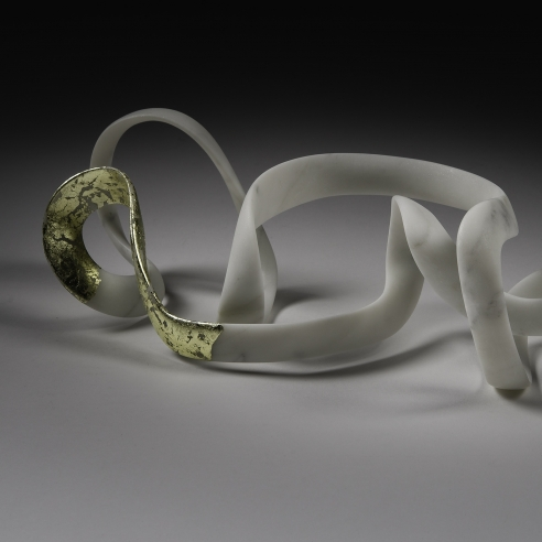 a sculpture by Elizabeth Turk of a thin looping bands of marble, a corner of which is covered in gold leaf