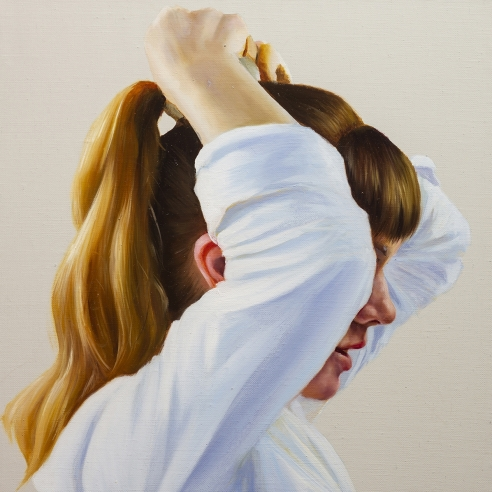 portrait of a woman with a pony-tail and arms raised, blocking her face