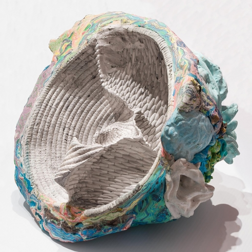 a sculpture by Lily Cox-Richard of basket forms pressed together inside a shell of multicolored swirls