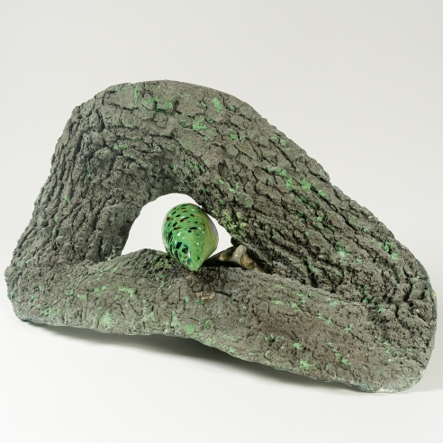 a sculpture by Lily Cox-Richard of cast tree bark with a green tongue-like form emerging from a knot in the center